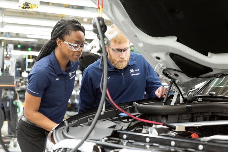 Two PACE Program associates are doing a quality check under the hood of a vehicle.